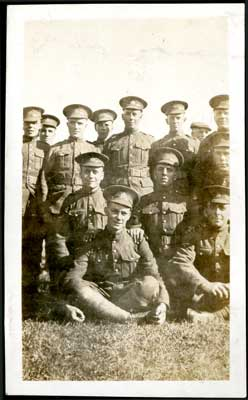Photograph of 12 soldiers with 2 seated on the grass