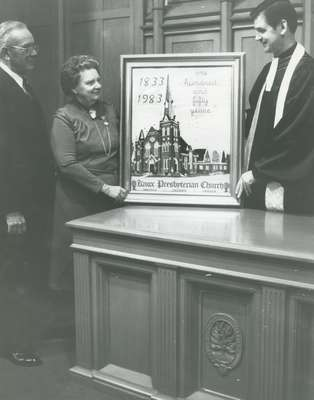 Rev. Cam Taylor, (right) with Walter Adamson, clerk of Session, and wife Dorothy Adamson beside her gift to the congregation of a petitepoint design of Knox Church on the 150th anniversary.