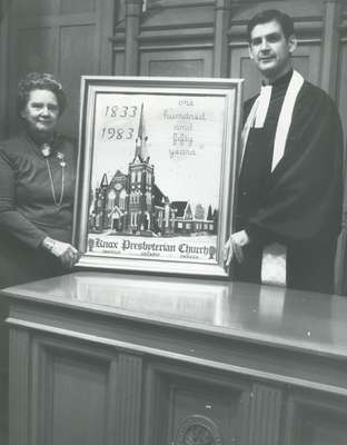 Rev. Cam Taylor (right) with Dorothy Adams (left) with her gift to the congregation of a petitepoint design of Knox Church for the 150th anniversary of the church.