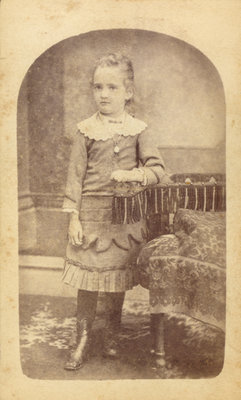 Little Girl Standing Next to an Elaborate Chair