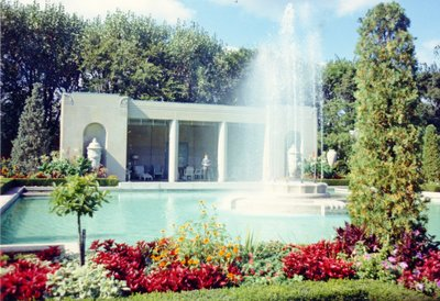Photo of a pool with fountain surrounded by flowers and hedges.