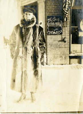 LH1317 J. Aubrey Morphy in fur coat with pipe in front of store
