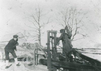 Hollis and Charlie Chant Operating a Dragsaw