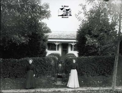 Two Women and a Man Posing with Small House, c. 1902-1906