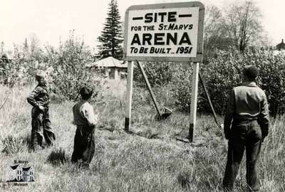 Boys looking at sign proclaiming future arena site, ca. 1949-50