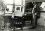 W. A. Kingsland watching William Jacobi at desk alleged to have been used by Thomas Edison