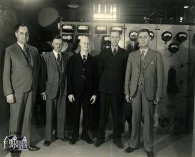 Five men standing in front of a transformer, 1936