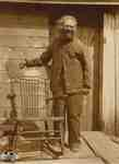 James (Jimmy) Tate standing beside his rocking chair