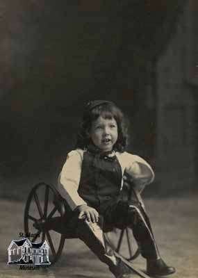 Boy sitting in two-wheeled cart