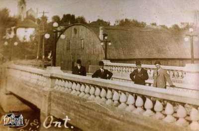 Four men standing on Wellington Street bridge