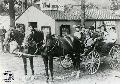 Buggy full of people posed in front of a photo studio building