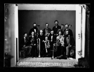 Group portrait of 11 men with musical instruments.