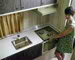 Unidentified Woman Next to a Kitchen Stove