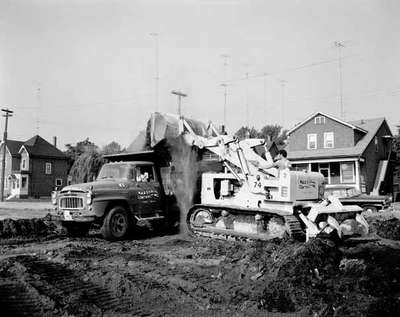 Marshall Contracting doing road repair using an IHC truck, model B180?, and IHC TD15 crawler tractor with a tractor mounted shovel, outside the IHC General Office in Stoney Creek, Ontario.