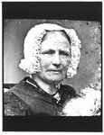 Bust portrait of an elderly woman in a white bonnet and silk brocade sleeve.