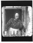 Portrait of an elderly woman standing in a doorway, behind a picket fence.