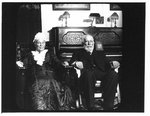 Portrait of seated elderly man and woman, in front of a piano.