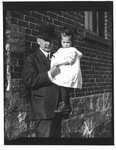 Outdoors portrait of John Connon holding a young girl.