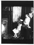 Portrait of John Connon with young boy and girl, seated by fireplace.