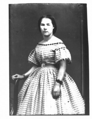 Portrait of a young woman in a checked dress.