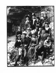Portrait of a group, predominantly women and children, on a rocky river bank.
