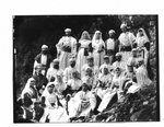 Group portrait of men and women in Arabian costumes, on a rocky river bank.