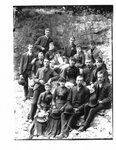 Group portrait of unidentified men and women on a rocky river bank.
