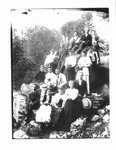 Group portrait of unidentified men and women on a rocky river bank in Elora.