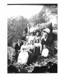 Group portrait of unidentified men and women on a rocky Elora river bank.