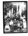 Group portrait of unidentified men, women and children in front of a house.