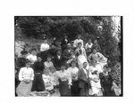 Group portrait of unidentified men, women and children on a rocky river bank in Elora.
