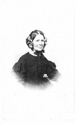 Portrait of a woman in a floral trimmed bonnet.