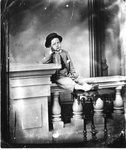 Studio portrait of an unidentified young boy sitting on a railing.