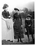 Outside portrait of a woman and two girls, standing on a boardwalk.