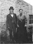 Outside portrait of Velvel Zeev Borovoy and wife Frieda Gittel Borovoy (nee Schushter), standing in front of a stone building.