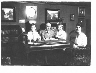 Portrait of an unidentified man, woman, and two children seated around a library table, Connon photographs are on the wall.