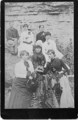 Outside portrait of a group of women, and one man, against a rocky background.