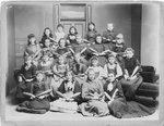 Group portrait of young women and girls holding Indian clubs.