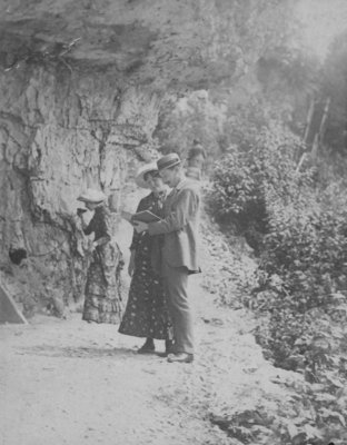 A man and woman look at an open book, while another woman drinks from a spring in the Elora rocks.