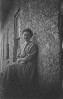 Portrait of a woman seated against a stone wall.