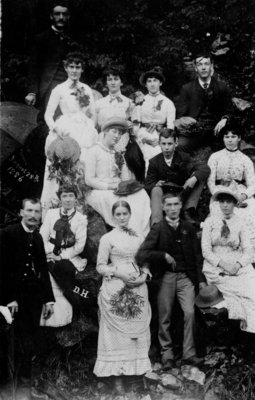 Group portrait of unidentified young men and women, on a rocky bank.