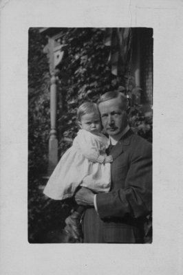 Portrait of John Connon holding a small child in a light coloured dress.