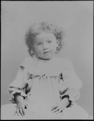 Portrait of a young child, with shoulder length curly hair.