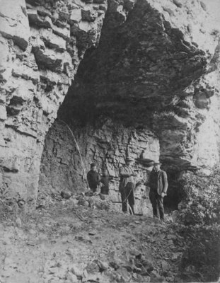 Two men and two boys standing against the rock of the Elora Gorge