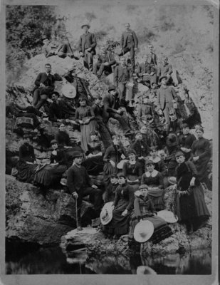 Large group of men and women posed on rocky river bank.