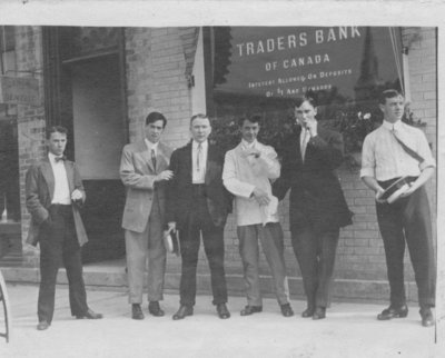 Group portrait of unidentified young men standing in front of the Elora branch of the Traders Bank of Canada.