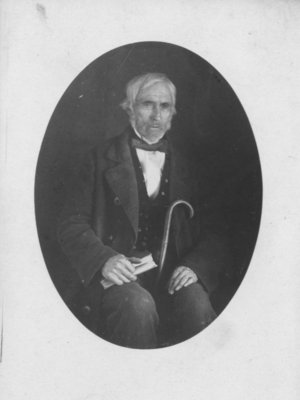 Portrait of an unidentified man, seated with book and cane.