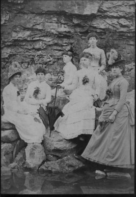 Group portrait of six unidentified young women, posed on a rocky river bank.