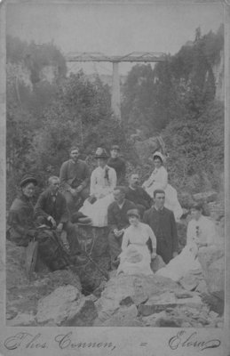Group of unidentified men and women posed on a rocky bank, with the bridge over the Irvine River, Elora, in the background.