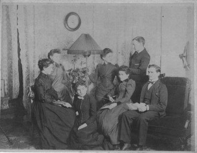 Group portrait of 2 men and 5 women in a living room/parlour.